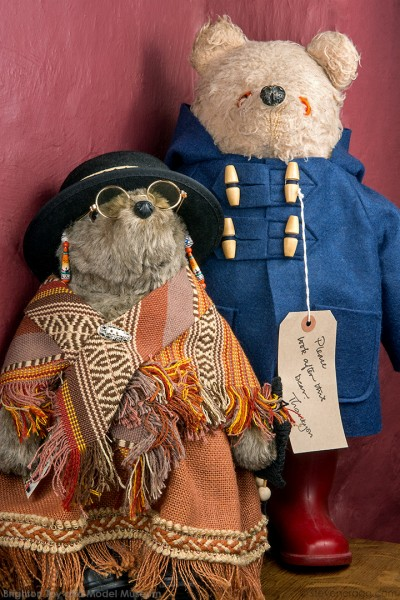 Photo of two teddy bears, old lady bear in hat, glasses and shawl stands in front of Paddington with blue duffle coat and red boots