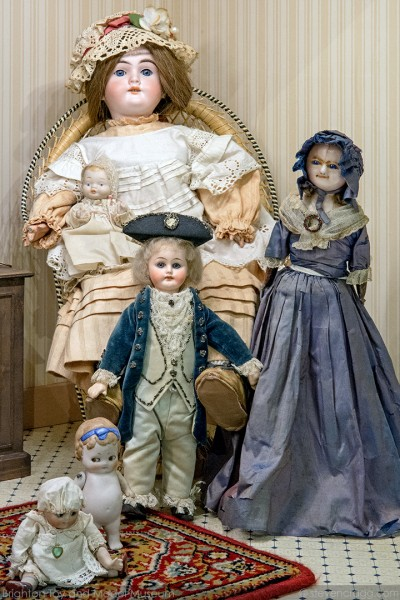 Photo of six different sized vintage dolls in period clothing