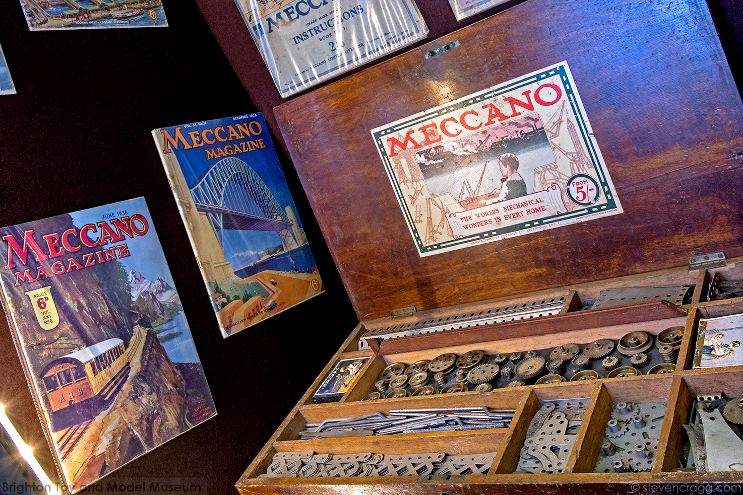 Photograph at an angle of an open box of Mexxano on the right and copies of Meccanno magazine on the left