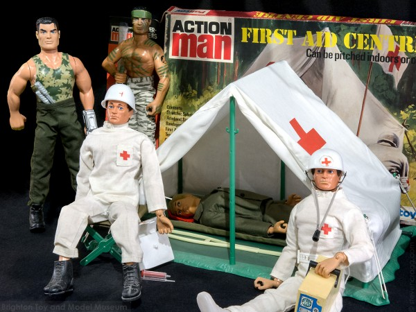 "Two Action Men dressed as doctors with another Action Man lying on a stetcher in a medical tent. Two army themed Action Men stand near by with a box which reads ""Action Man - First Aid Centre"""