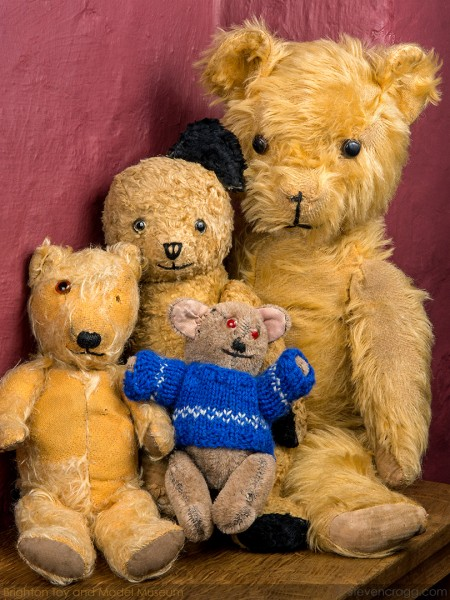 Four different sized traditional light brown bears, threadbare and missing some eyes and ears. The smallest one wears a blue knitted jumper.