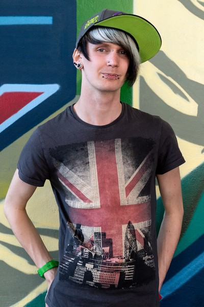 Heaad and torso shot of Matt born in Brighton in 1991. He wears a green and black cap and a tee shirt with the Union Flag and London motif. He has some piercings on his face