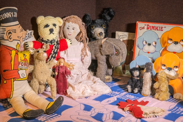 "Various hand made toys including a fabric Sunny Jim soldier, knitted and felt animals and dolls and a box which reads ""The Dinkie"" with images of cartoon dogs"