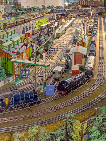 A toy train scene including railway tracks, a station and various carriages