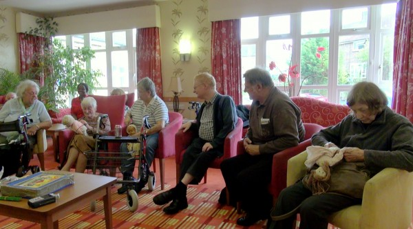 New Larchwood Reminiscence group, four women and two men talking, looking at dolls
