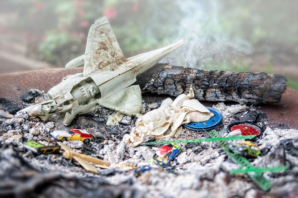 Shot of some smashed toys, an aeroplane and some toy cars, sitting on burnt ash with a smoking log