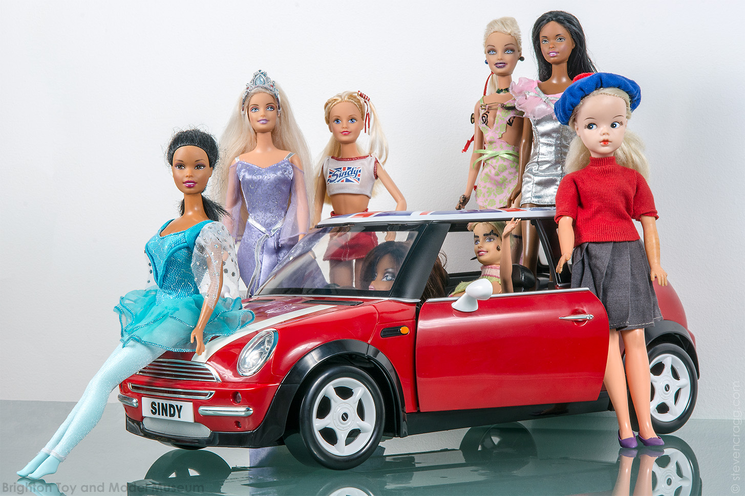 Sindy car - a red mini with Union Flag on the roof - with two dolls inside and six dolls standing outside from various eras